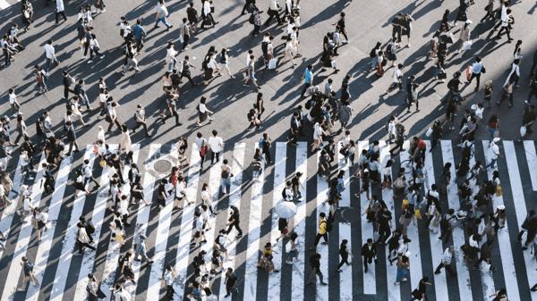 Luftaufnahme von Menschenmasse auf einem Zebrastreifen.