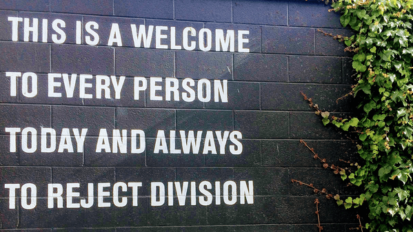 "Text an einer Wand: ""This is a welcome to every person today and always to reject division."""