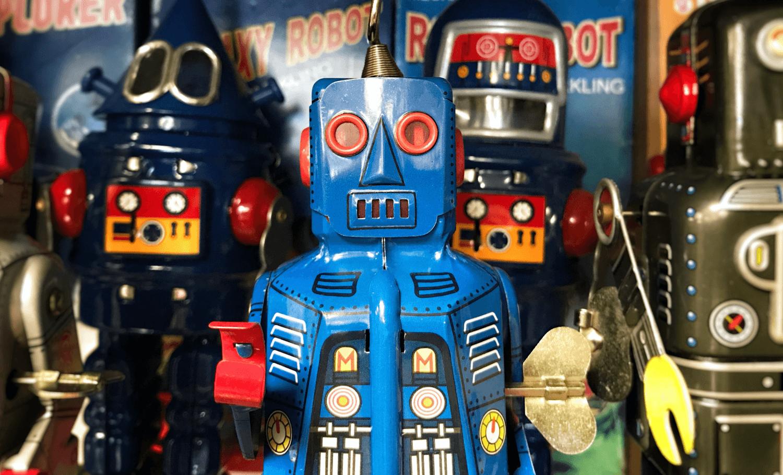 Vintage Spielzeugroboter vor Comicbüchern