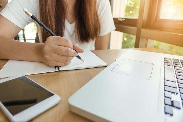 De_unymira_Blog_ Tipps und Tricks für perfekte WIssensinhalte 600x400_Frau aufschreiben vor Laptop